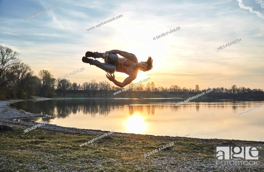 Stock Photo: Germany, Bavaria, Feldkirchen, man doing parkour at lakeshore.