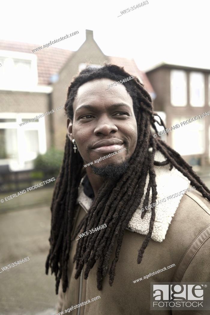 Stock Photo: content African man walking in residential district in Leeuwarden, Friesland, Netherlands, Europe.