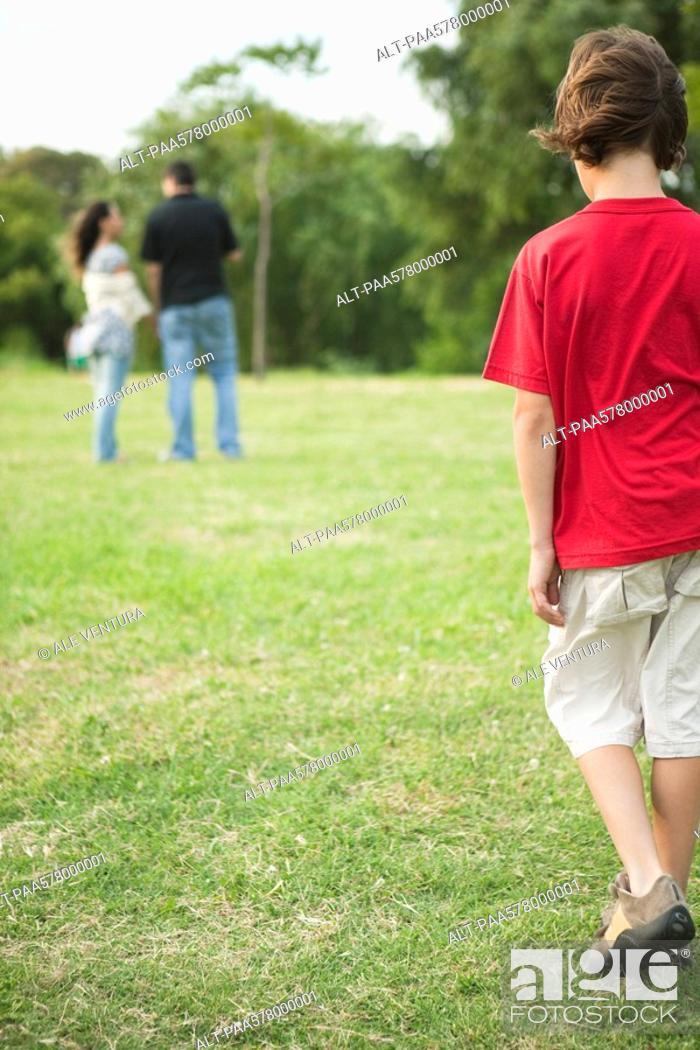 Stock Photo: Boy walking sulkily toward parents having conversation distance.
