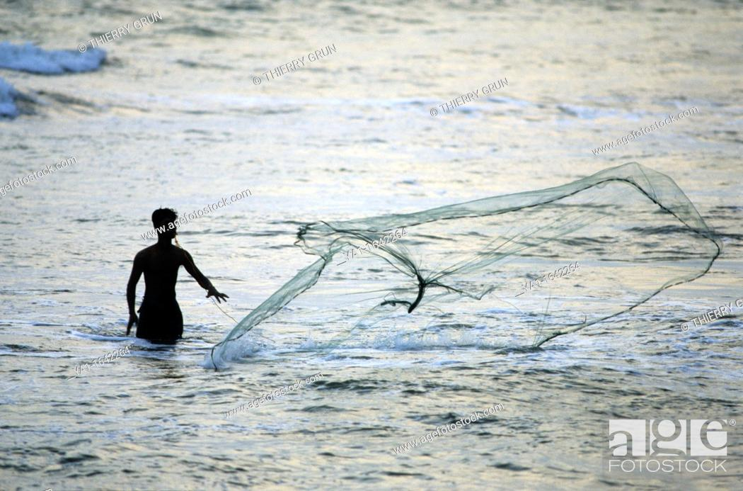 Stock Photo: Local fisherman using a cast net in sea at dusk, Kalutara beach, Sri Lanka.