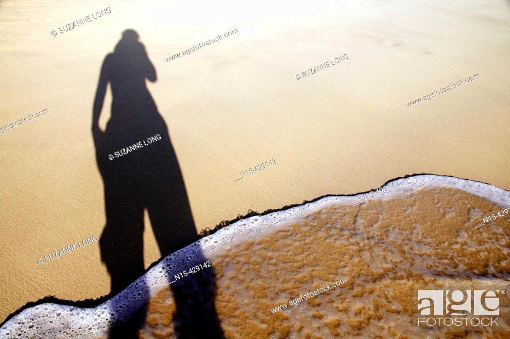 Shadow Of Woman Standing In The Waves On White Sand Beach Stock