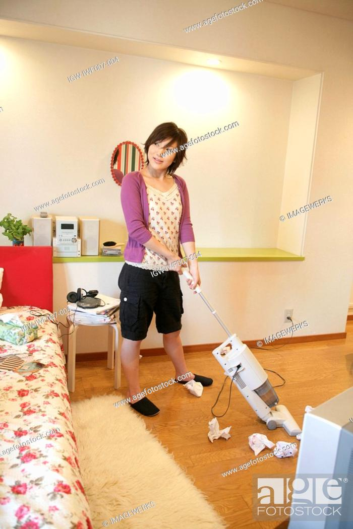 Stock Photo: A young woman in cropped pants, vacuuming her room.