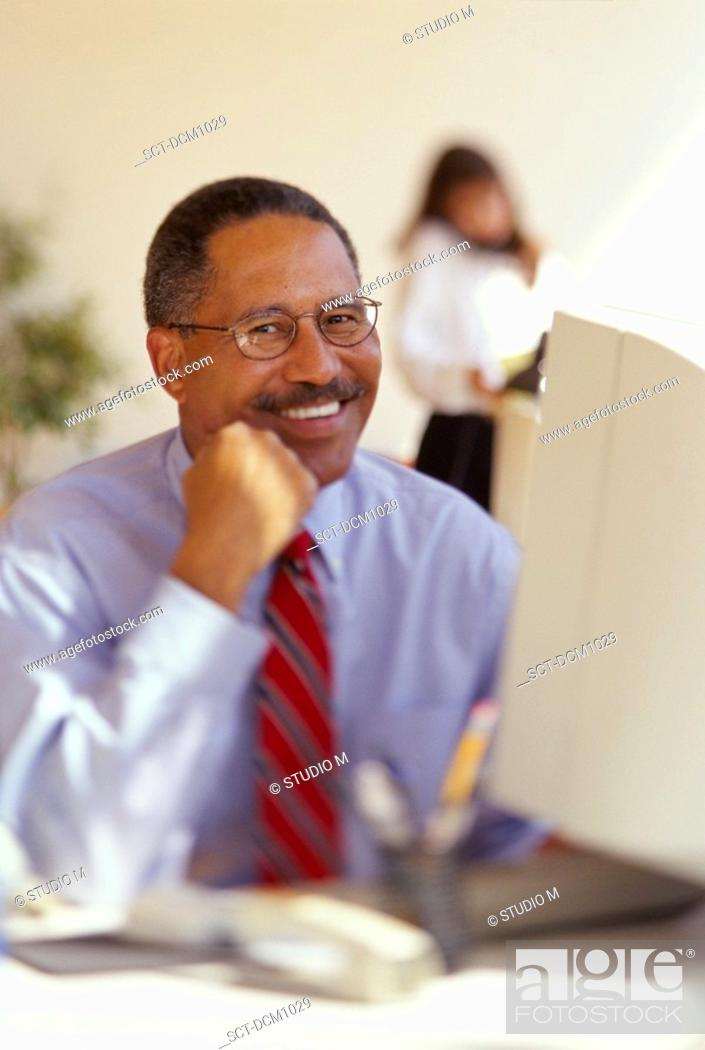 Stock Photo: Male African-American executive sitting at his desk and smiling.