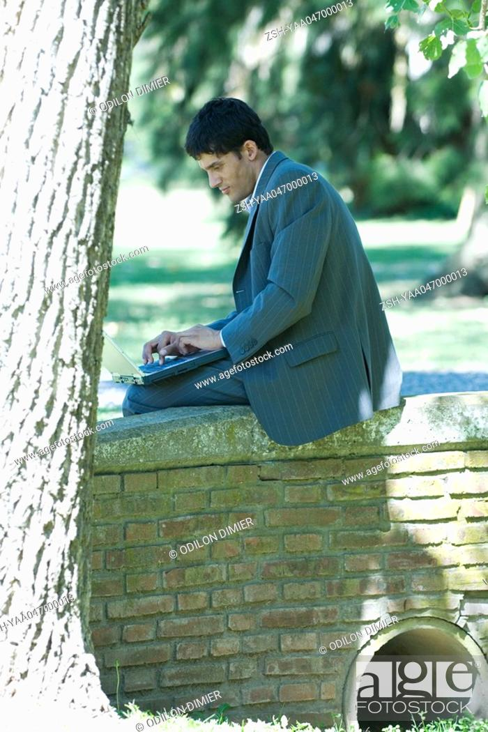 Stock Photo: Businessman sitting on low wall in park, using laptop.