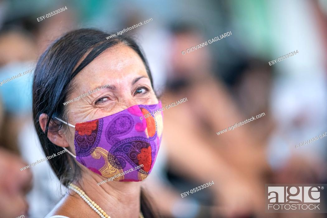 Stock Photo: Happy woman wearing mask at the stadium in Covid-19 time.