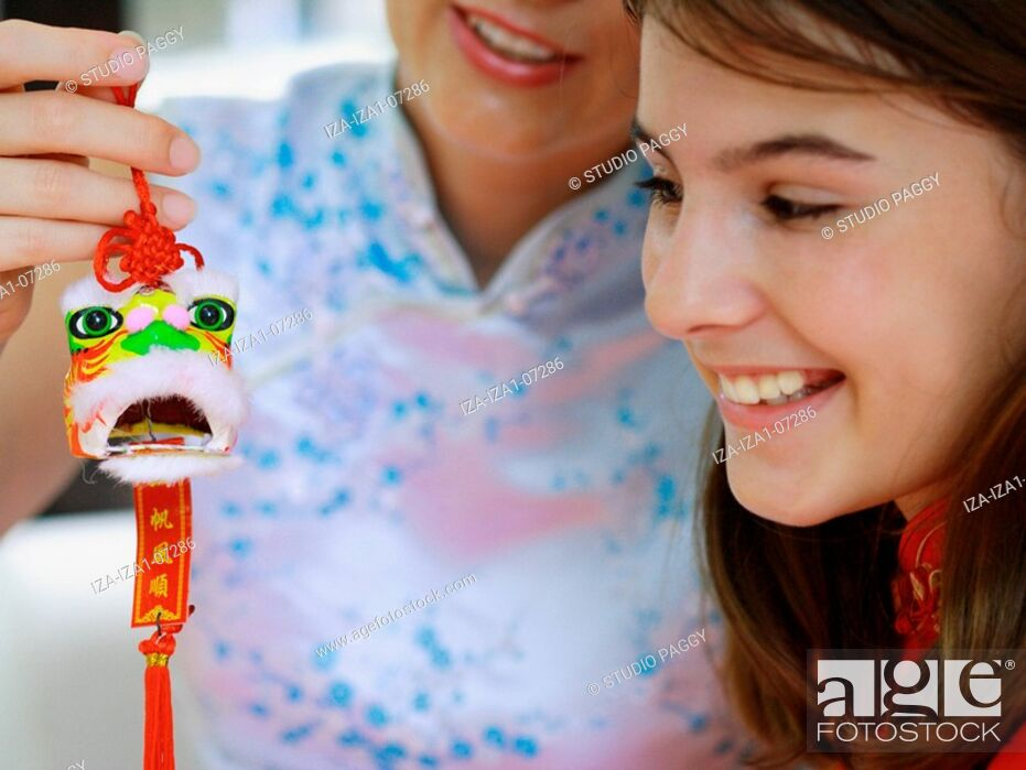 Imagen: Close-up of a teenage girl with her mother holding a good luck charm.