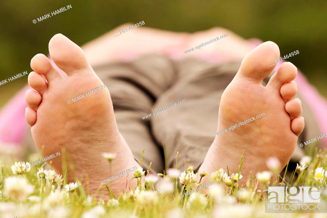 Stock Photo: Close-up of undersides of bare feet of woman lying on grass.