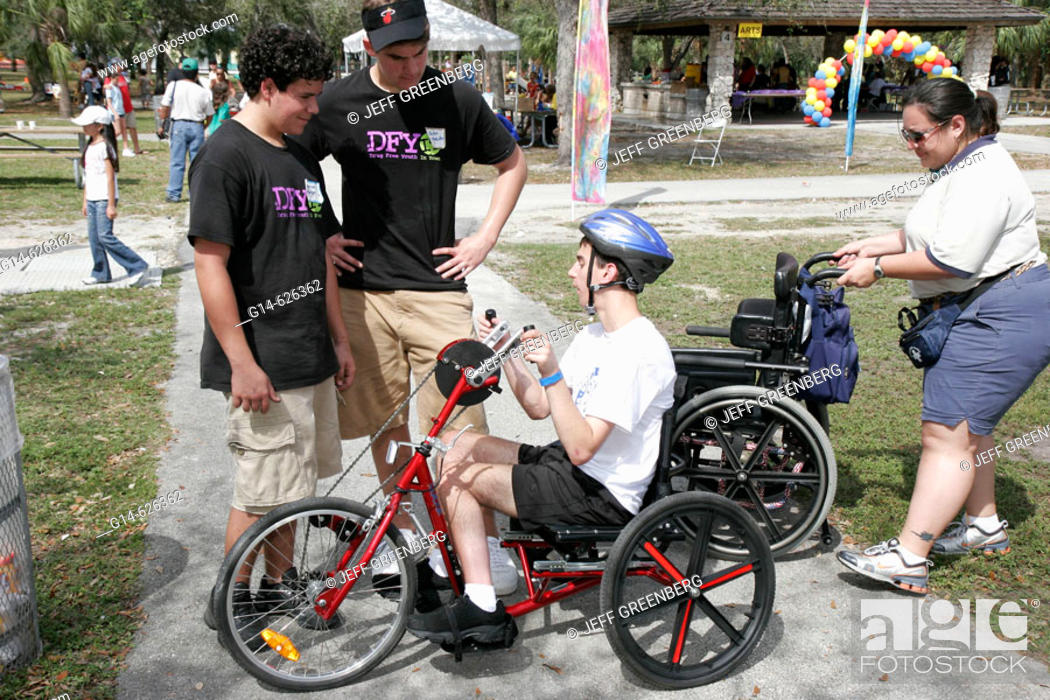 Stock Photo: Family Festival of the Arts, disabled children activities, arm powered tricycle, wheelchair. Kendall. Miami. Florida. USA.