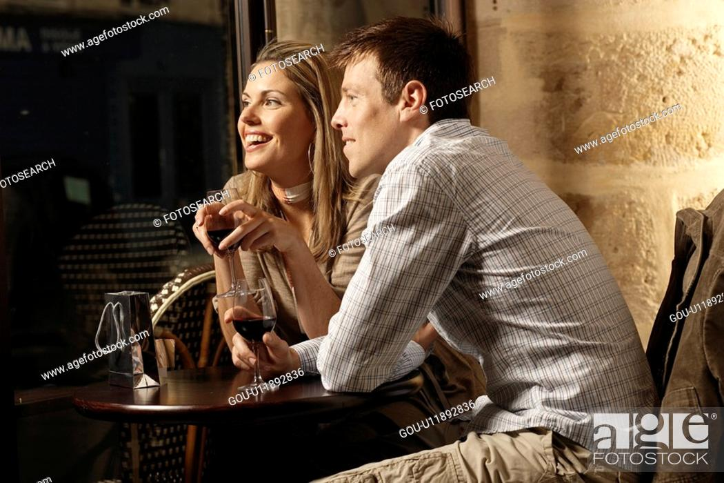 Stock Photo: Mid adult couple drinking red wine in restaurant.