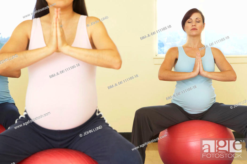 Stock Photo: Pregnant women meditating on exercise balls.