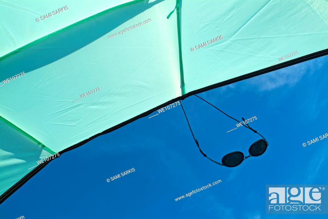 Stock Photo: Sunglasses suspended from a sunshade against a blue sky.