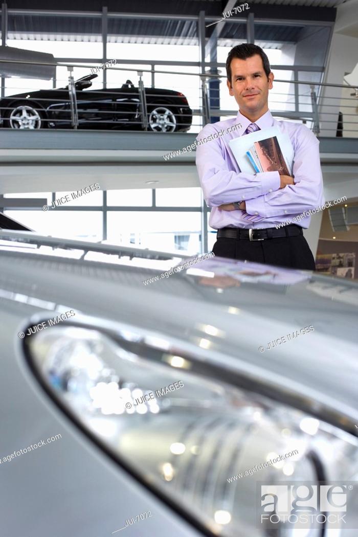 Stock Photo: Car salesman standing beside new saloon cars in showroom, holding brochure, smiling, portrait.