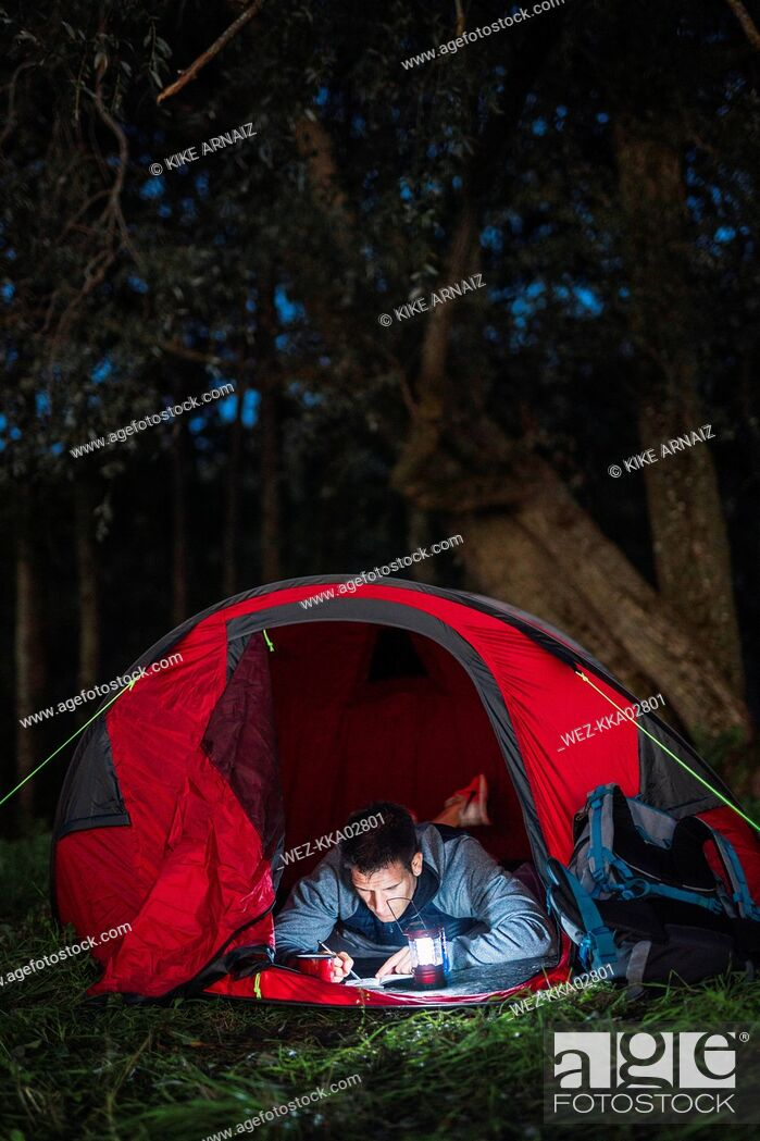 Stock Photo: Man camping in Estonia, drawing in his sketchbook at night.
