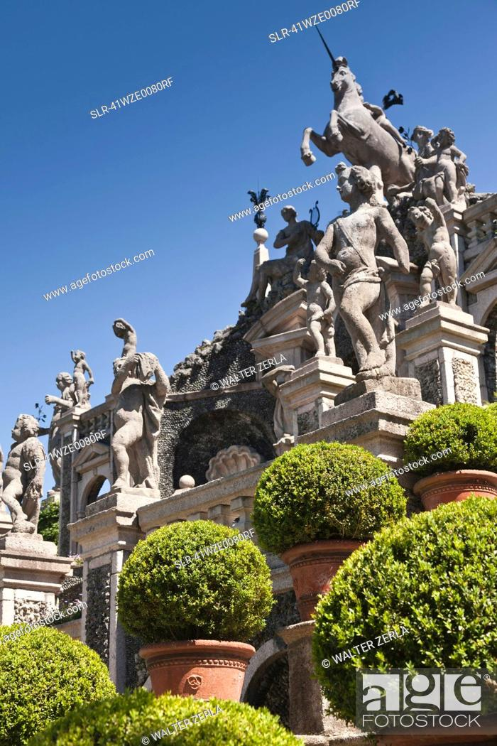 Photo de stock: Shrubs with ornate statues and columns.