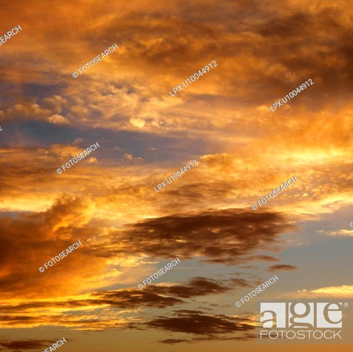 Stock Photo: Golden clouds in sky with sunset.