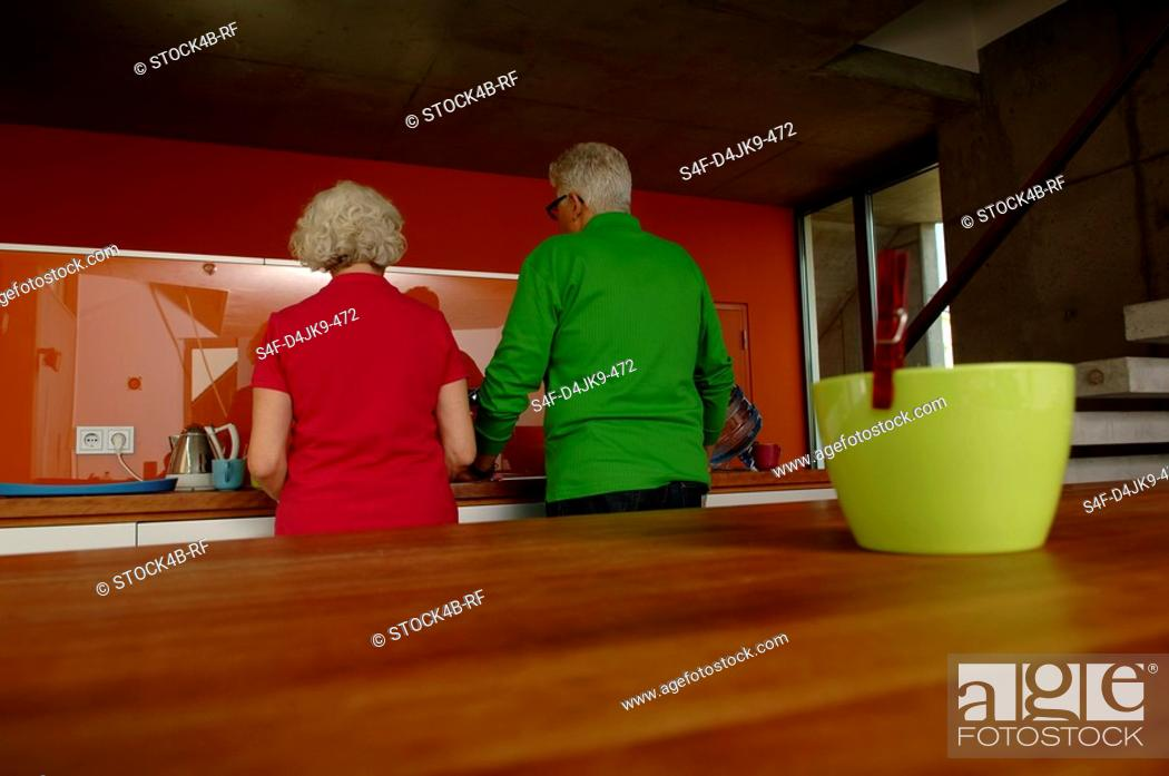 Stock Photo: Senior couple standing in domestic kitchen.