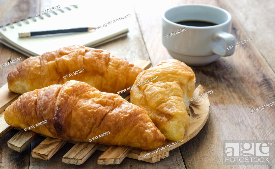 Stock Photo: Croissants coffee notebook and pencil on the wooden table - tone vintage.