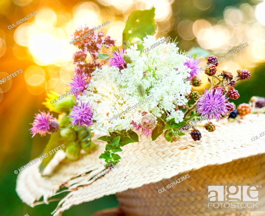 Stock Photo: Freshly picked wildflowers with hazelnut and blackberry plants in straw hat.