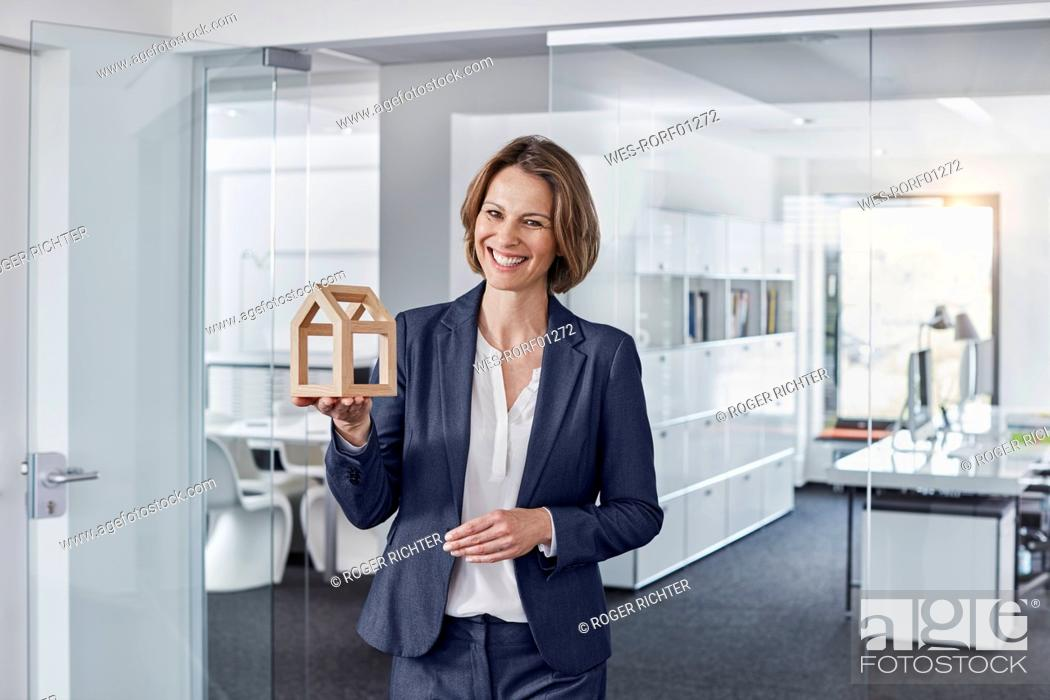 Stock Photo: Portrait of smiling businesswoman holding architectural model in office.