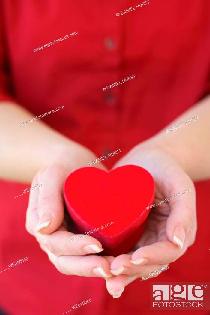 Stock Photo: Hands holding heart shaped box.