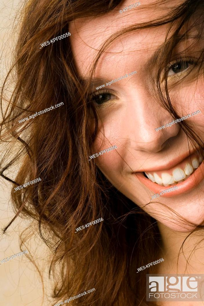 Stock Photo: Young woman, Smiling, unkempt hair, close up.