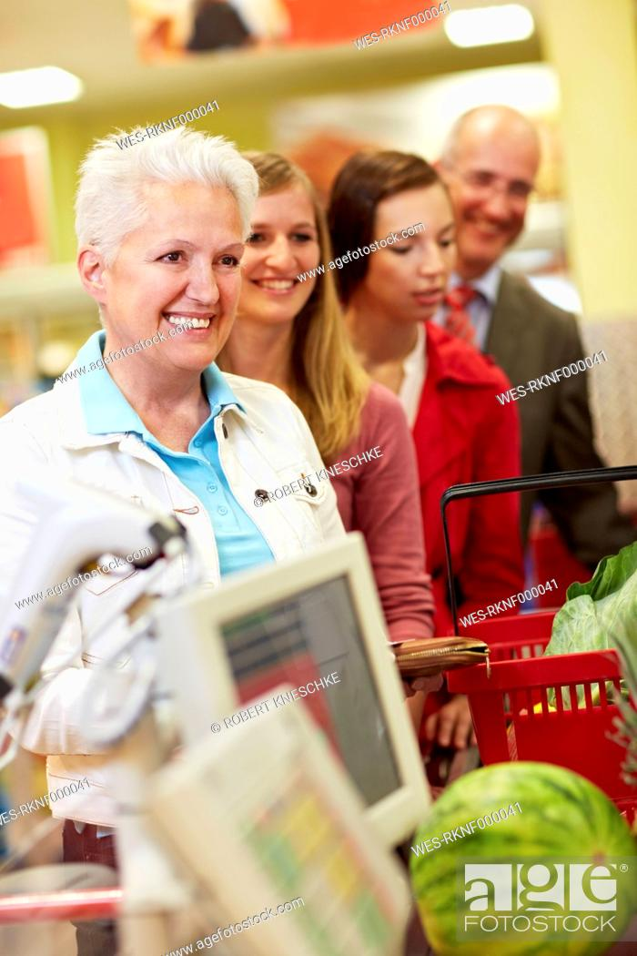Stock Photo: Germany, Cologne, Man and women waiting in supermarket.