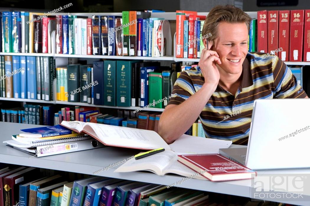 Stock Photo: Young man studying in library, smiling, close-up.
