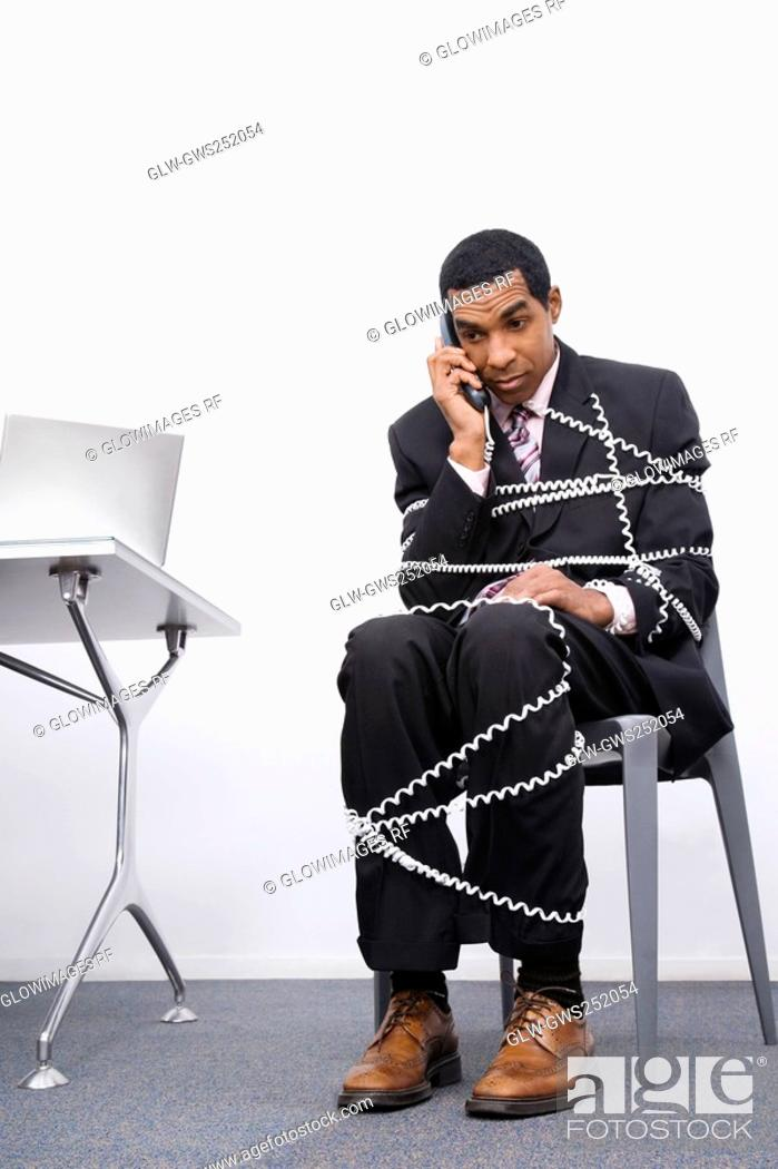 Stock Photo: Businessman trapped in a wire of a telephone.