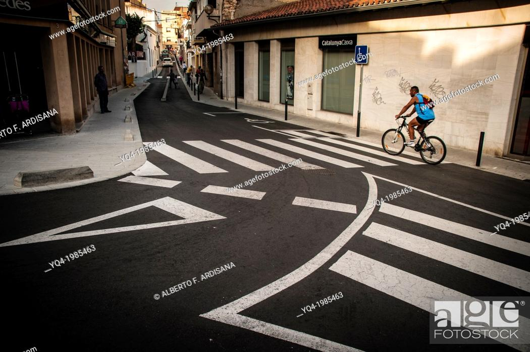 Stock Photo: A man riding his bicycle down a street in Cubelles, Catalonia, Spain.