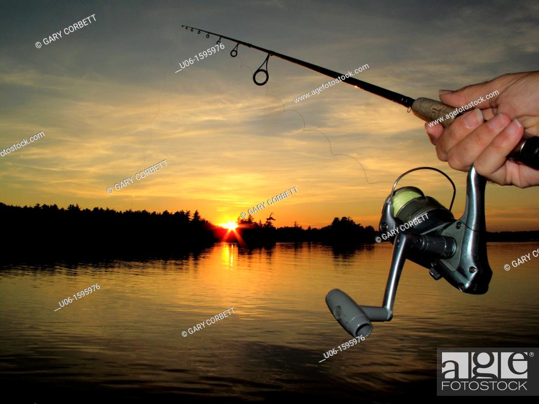 Stock Photo: A fishing rod and reel with a sunset on a lake in background.