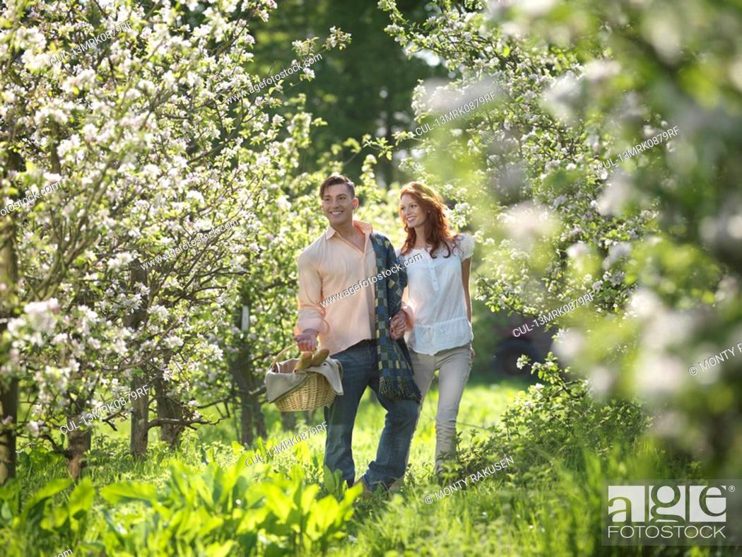Stock Photo: Couple With Picnic In Orchard.