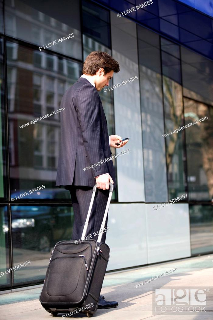 Stock Photo: A businessman pulling his suitcase, using his mobile phone.