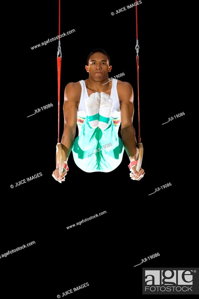 Stock Photo: Male gymnast performing on gymnastic rings, portrait.