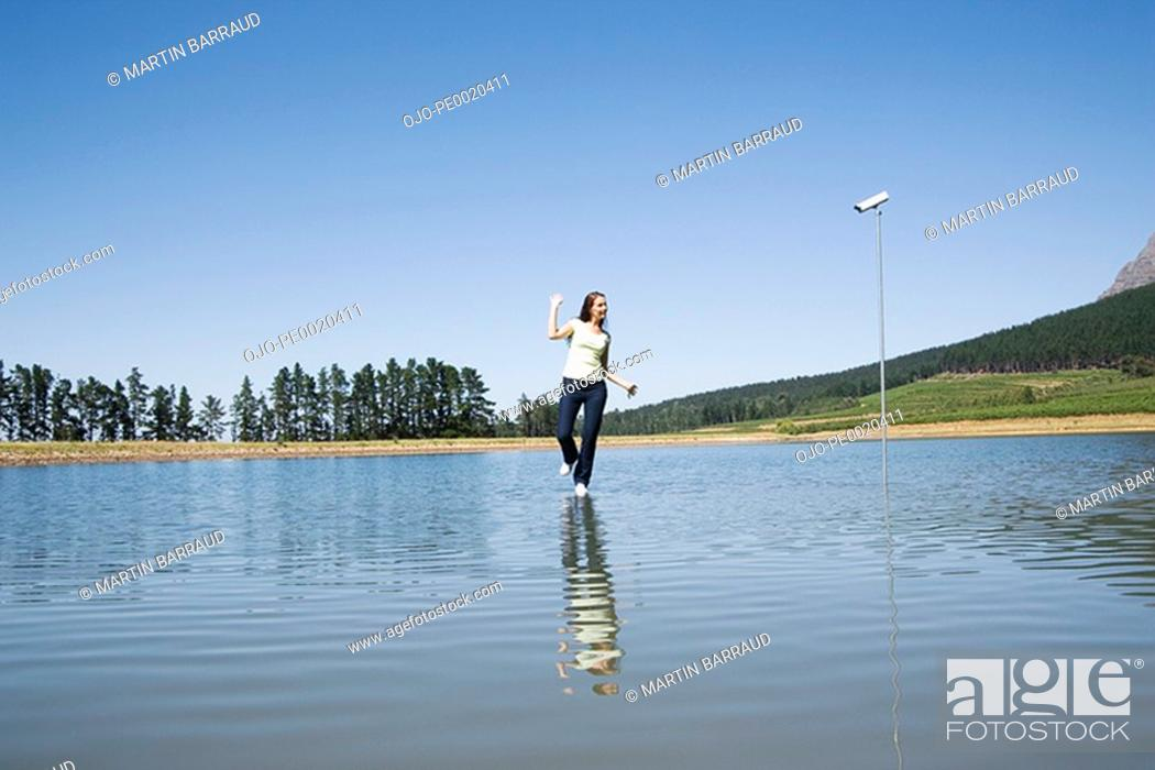 Stock Photo: Woman dancing on water with surveillance camera and trees.