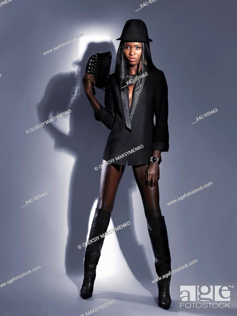 Stock Photo: Attractive young woman wearing a black jacket and high stiletto boots  High fashion photo.
