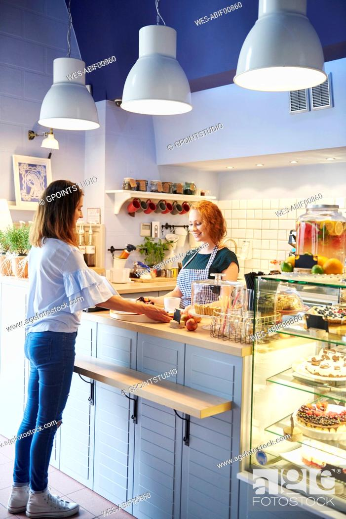 Stock Photo: Customer and waitress at counter in a cafe.