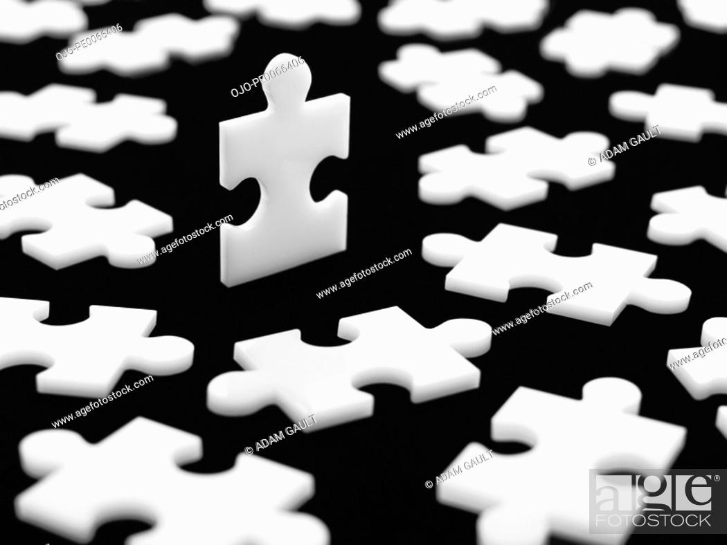 Stock Photo: Scattered puzzle pieces with one piece upright.