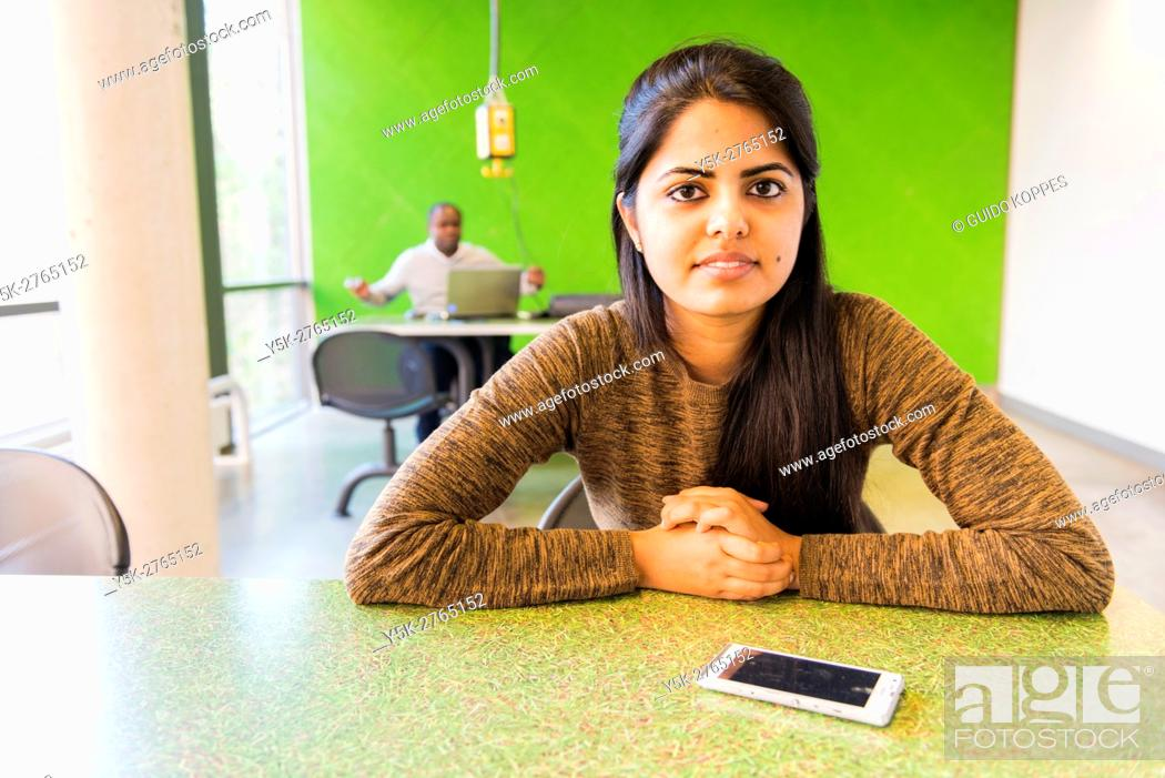 Stock Photo: Aachen, Germany. Young, Indian university Exchange student with her smartphone at a dormatory workdesk.