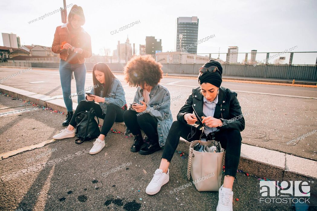 Stock Photo: Friends sitting on kerb texting, Milan, Italy.