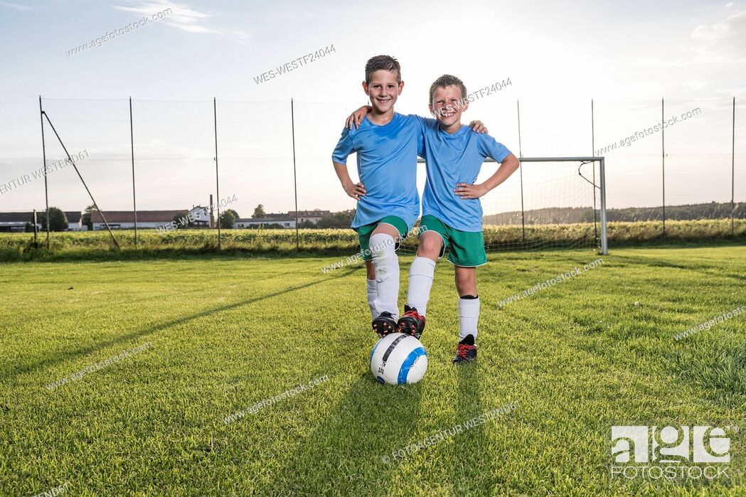 Stock Photo: Smiling young football players embracing on football ground.
