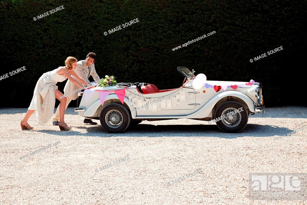 Stock Photo: Newlyweds pushing broken down vintage car.