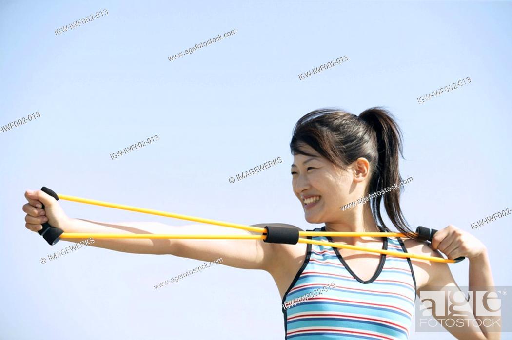 Stock Photo: A woman working out as she stretches a rope tightly with her hands.