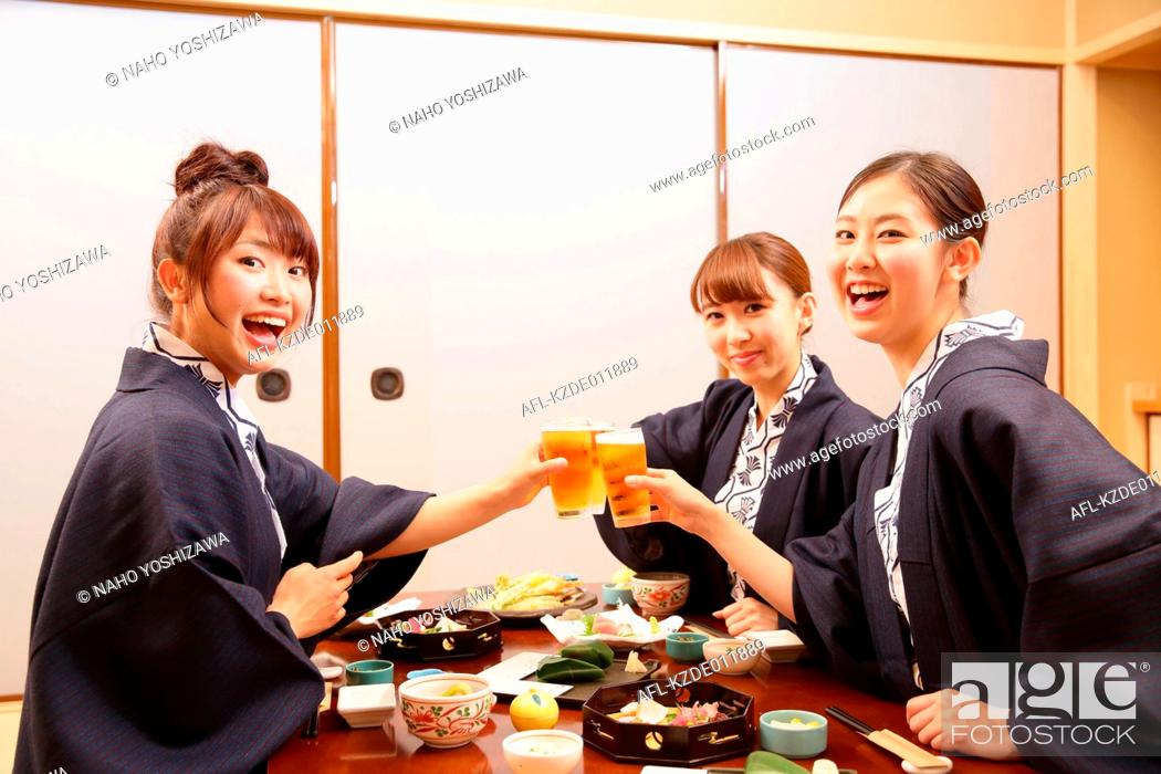 Stock Photo: Young Japanese women wearing yukata eating at traditional ryokan inn.