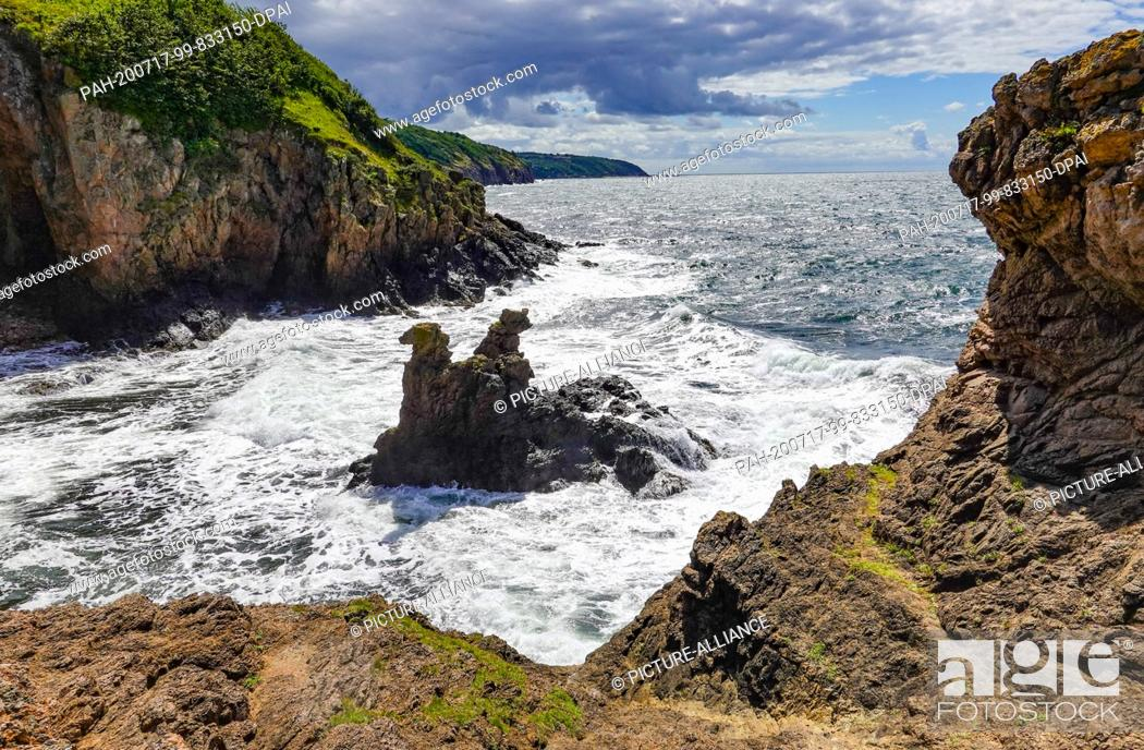 Stock Photo: 08 July 2020, Denmark, Allinge: The Camelhovederne and Lövehovederne (Camel head and Lion head rocks) rise from the Baltic Sea on the cliffs below the castle.