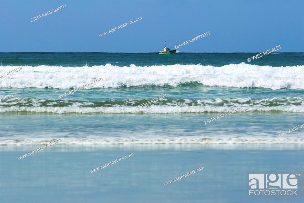 Stock Photo: Sea shore, fishing boat on horizon.