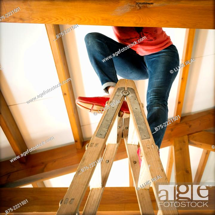 Stock Photo: Unrecognizable woman legs on a ladder inside a house with wooden beams.