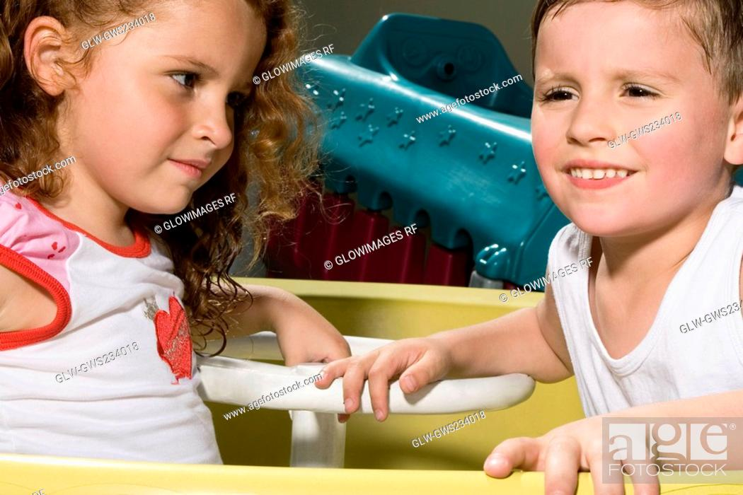 Stock Photo: Side profile of a boy and a girl sitting in a toy car.