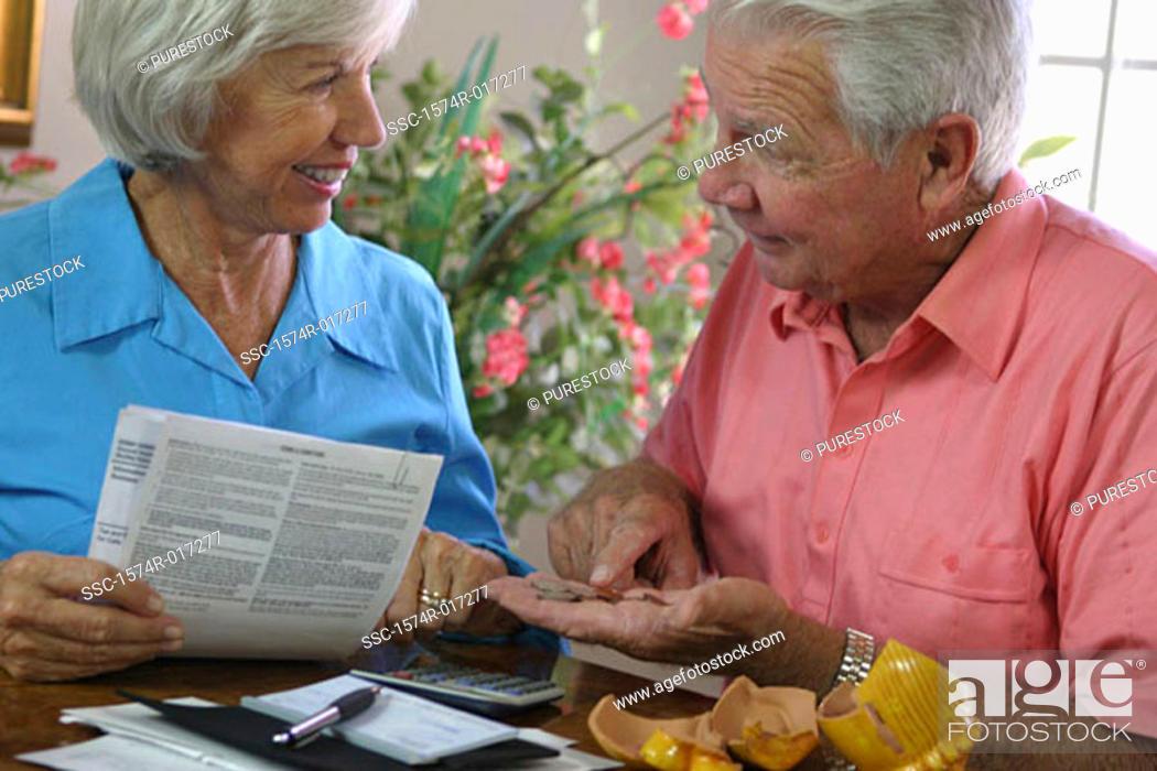 Stock Photo: Senior woman holding a bill looking at a senior man.