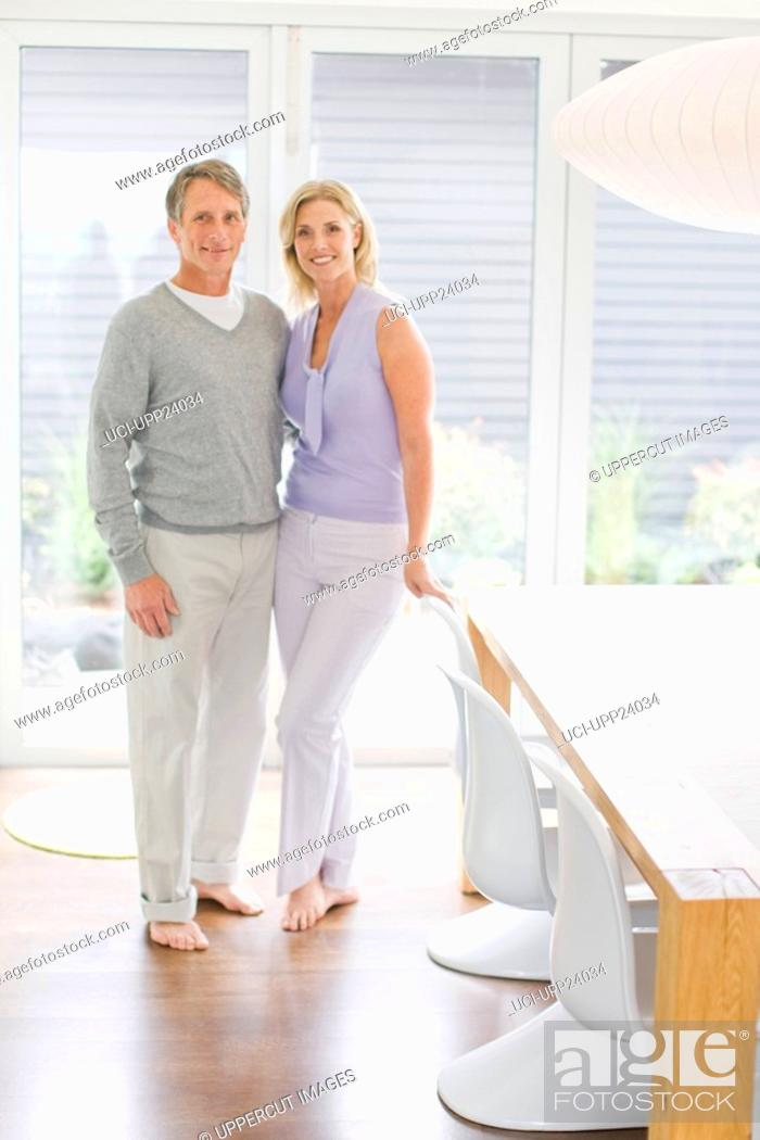 Stock Photo: Portrait of couple standing in dining room.