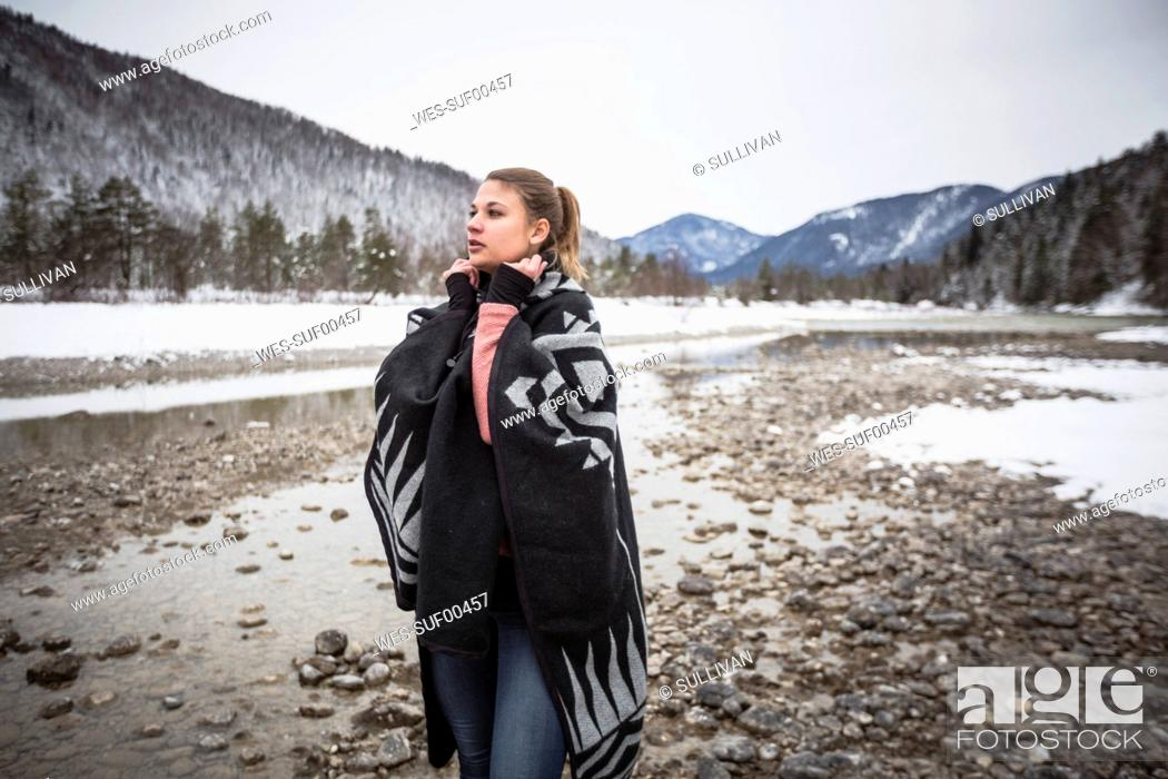 Photo de stock: Young woman standing at a river in winter.